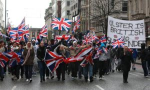 Loyalists march in Belfast waving British Union flags